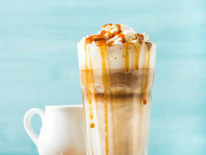 Latte macchiato with whipped cream and caramel sauce in tall glass on round wooden serving board over blue painted wall background, selective focus, vertical composition