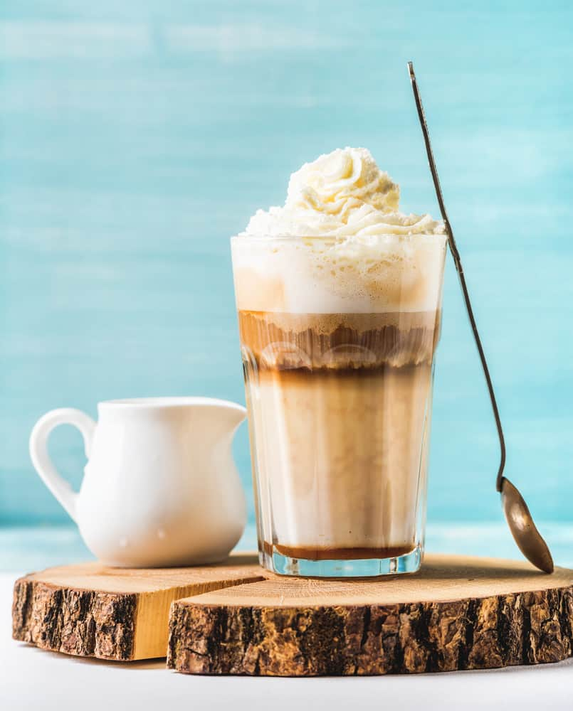 Caramel Latte with whipped cream, serving silver spoon and white pitcher on wooden round board over blue painted wall background, selective focus, vertical composition