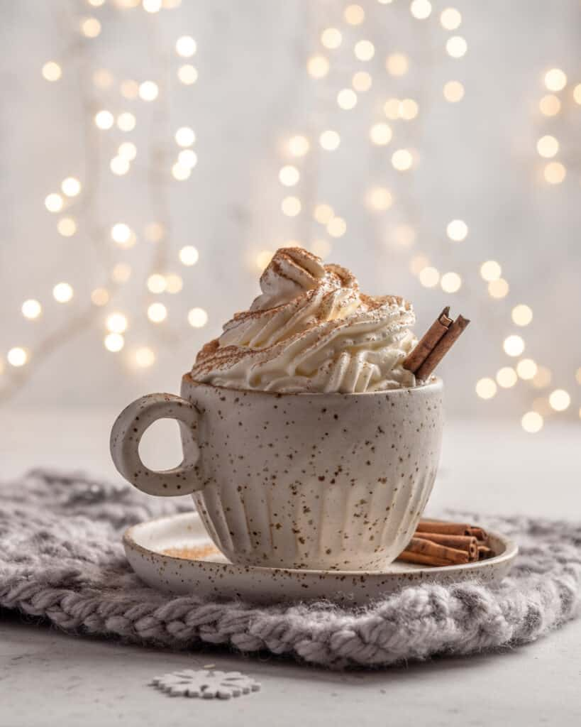 Gingerbread Latte  with cream and cinnamon stick in a ceramic cup.